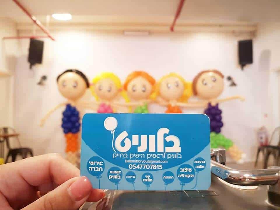 תמונה של כרטיס ביקור בצבע כחול של בלוניט כאשר ברקע מופיעות בובות מבלונים