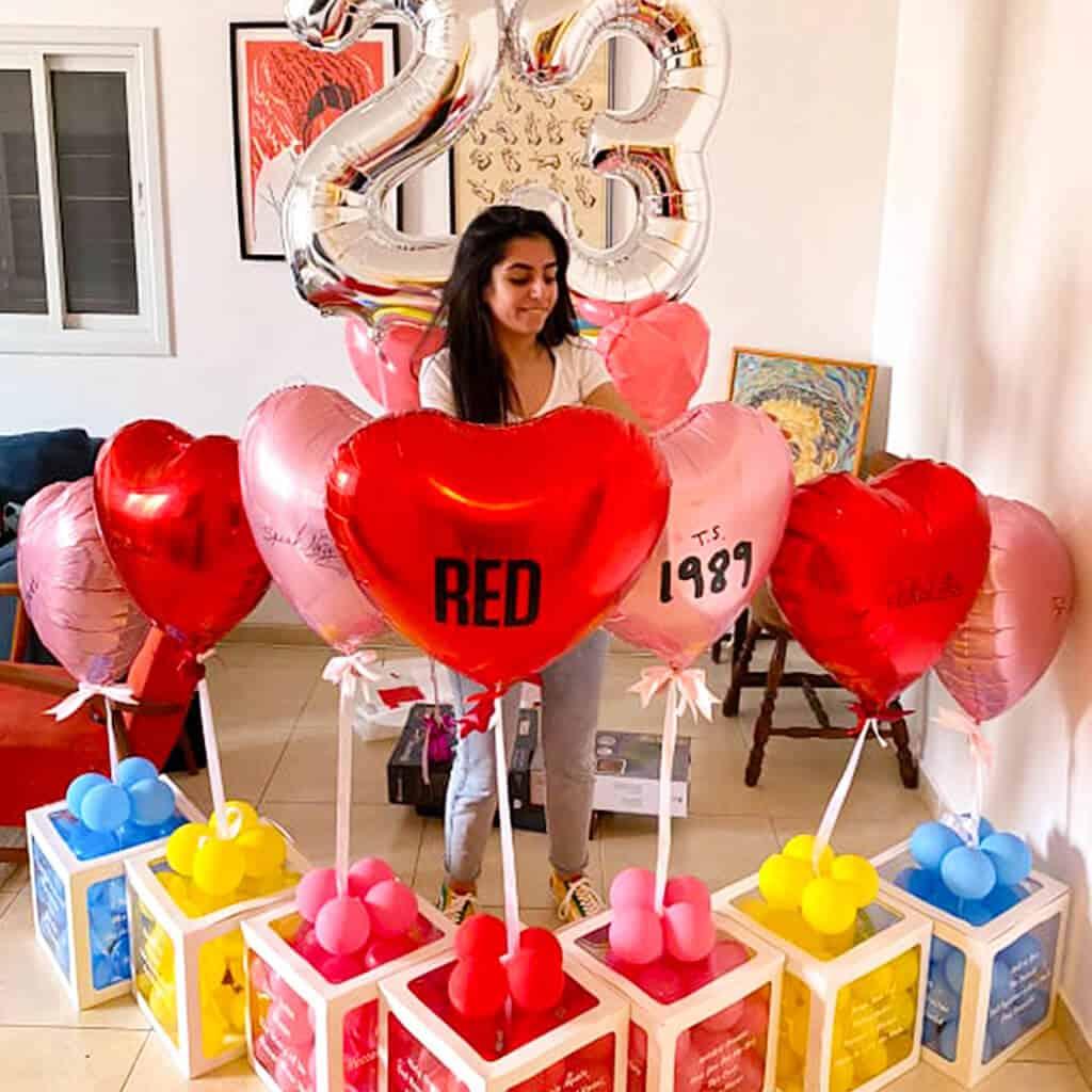 בלונים עבור מעריצה של טיילור סוויפט עם כל שמות האלבומים והשירים של הזמרת מודפסים על מארזי ברכות עם בלונים בצורת לב והספרות 23