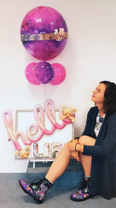 יוליה טישין יושבת ליד בלונים בצבעי ורוד ולבן