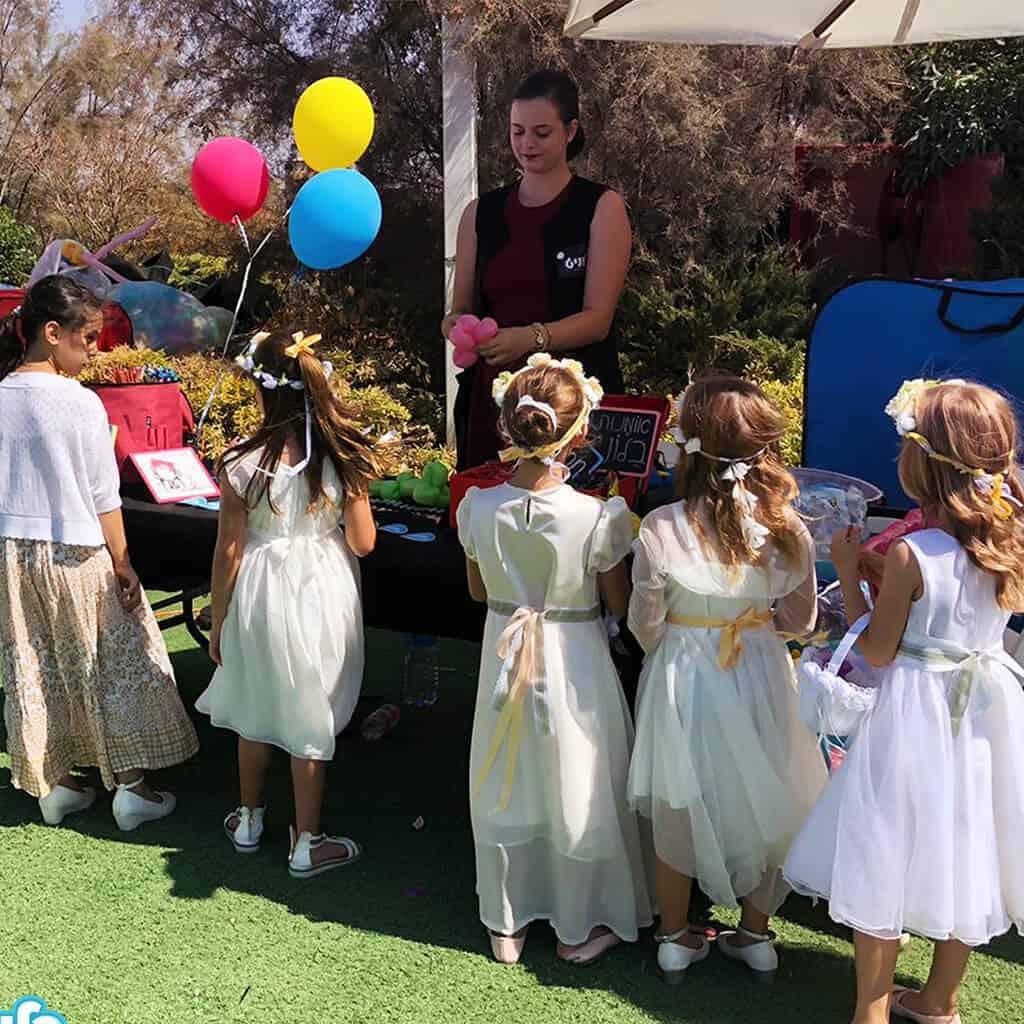 אמנית בלונים מחלקת לילדות עם שמלות לבנות בלונים